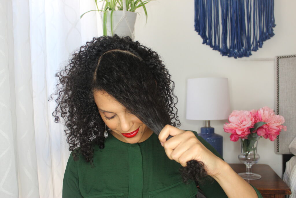 DiscoCurls holding her sectioned curly hair